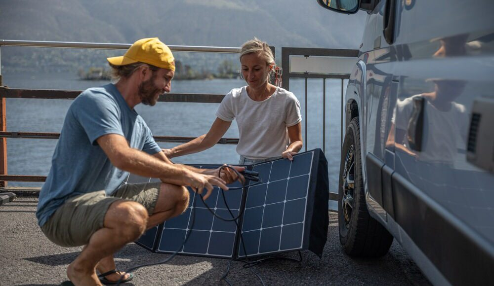 Two people installing a solar panel